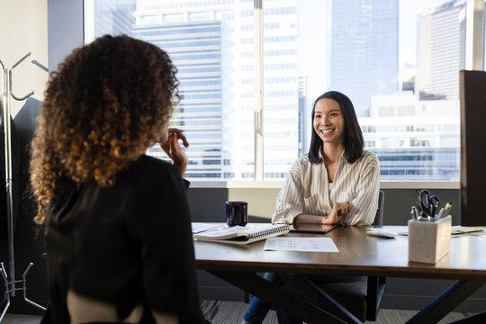 Smiling businesswomen talking at highrise office desk