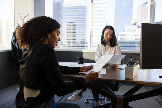 Businesswomen reviewing paperwork in highrise office