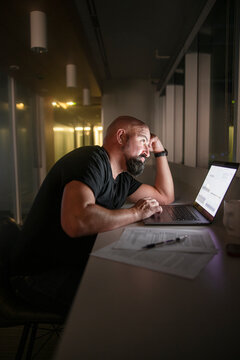 Tired businessman working at laptop in dark office