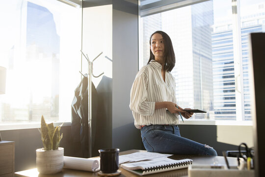 Confident businesswoman with digital tablet in sunny highrise office