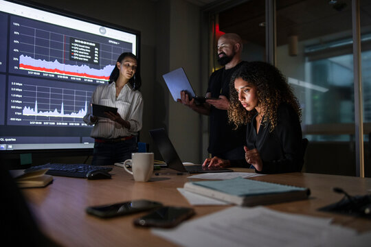 Business people reviewing data in dark conference room meeting