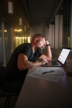 Tired businessman working late at laptop in dark office