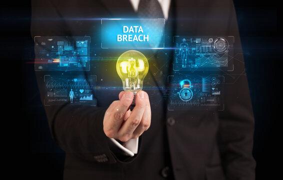 Businessman holding lightbulb with DATA BREACH inscription, online security idea concept