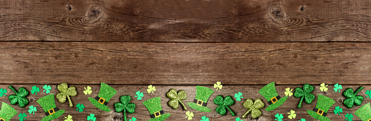 Obraz St Patricks Day shamrock and leprechaun hat bottom border. Top down view over a rustic wood banner background with copy space. - fototapety do salonu