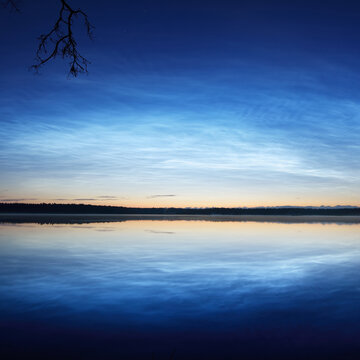 Starry sky with noctilucent clouds and fog above the Saimaa lake at summer solstice night. Tree silhouettes. Golden sunlight. Long exposure. Epic cloudscape. Symmetry reflections on the water. Finland