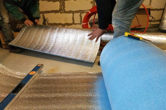 the installer and auxiliary worker wraps the air duct with mineral wool and foil