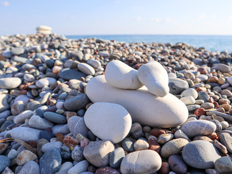 Composition of stones on the beach. The concept of resuming travel, upcoming summer vacation at sea.