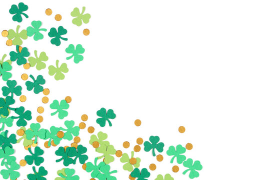 St Patricks Day shamrock and gold coin confetti corner border isolated on a white background with copy space