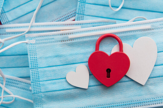Heart shaped padlock on a protective face mask. Covid valentines day concept