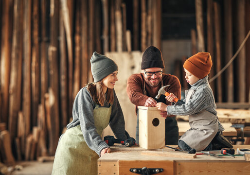Kid with parents assembling wooden bird house in craft workshop