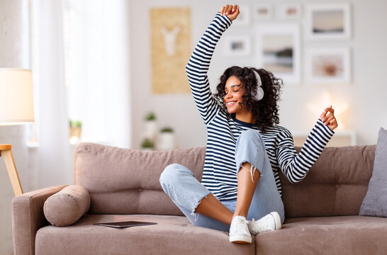 Happy ethnic woman listening to music and dancing on sofa