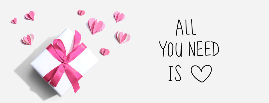 All you need is love message with a gift box and paper hearts