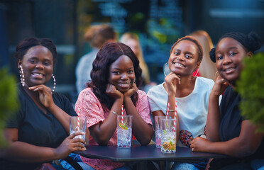 Fototapeta a group of beautiful happy african american women, girls chilling out at summer outdoor cafe, drinking cocktails and having fun obraz
