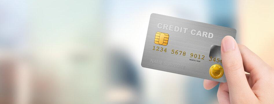 屋外でクレジットカードを持つ女性の手