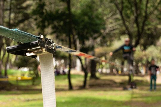 Hombre desenfocado haciendo equilibrio sobre una correa de nylon practicando Slacklining