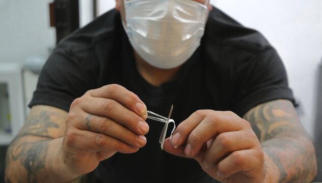 Perforación piercing en oreja lóbulo arete en estudio de tatuajes