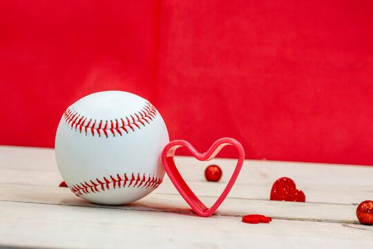 Baseball and red heart on red heart background for Valentine's Day