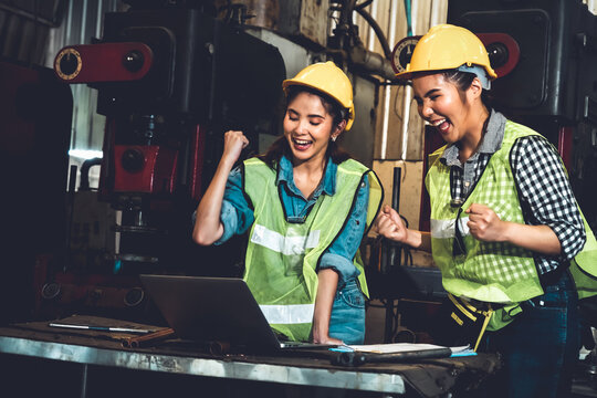 Two factory job worker celebrate success together in the manufacturing workshop or warehouse . Industry work achievement concept .