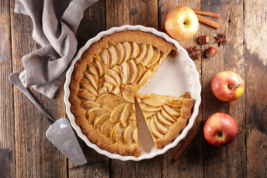 apple pie and spices on wood background