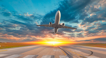 White Passenger plane fly up over take-off runway from airport at sunset