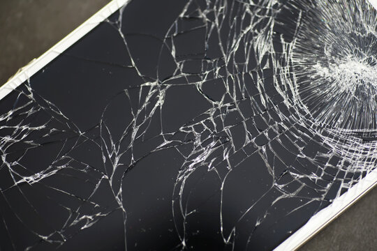 Crack on the glass. Broken screen. Broken phone. Cracked glass background. White cracks in the glass.