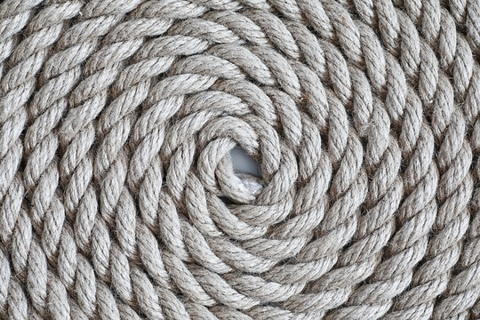 Braided thick rope tied in a skein. Hemp rope for decoration and design. Background from a fishing rope.