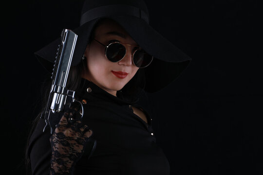 portrait of a sexy girl killer with a gun on a black background