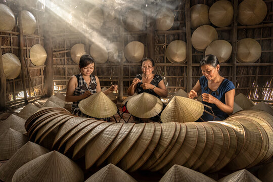 Group of Vietnamese female craftsman making the traditional vietnam hat in the old traditional house in Ap Thoi Phuoc village, Hochiminh city, Vietnam, traditional artist concept