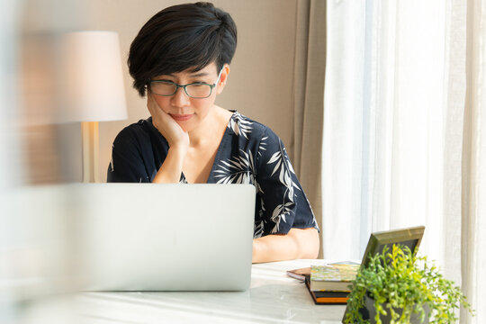 Portrait of beautiful middle-aged asian woman watching on demand movie, reading eBook, email and messages from her social media platforms with computer laptop at home during Covid-19 pandemic lockdown