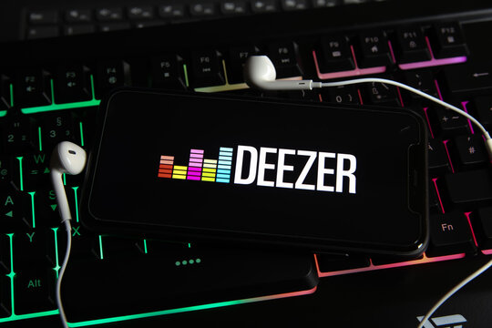 Viersen, Germany - January 9. 2021: Closeup of smartphone screen with logo lettering online music streaming service Deezer on computer keyboard
