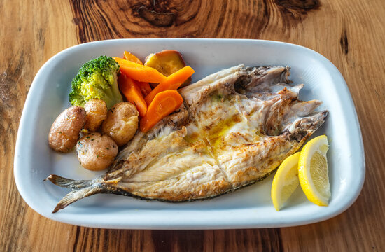 Grilled fish plate with some nicely roasted potatoes, carrots and broccoli on the side.