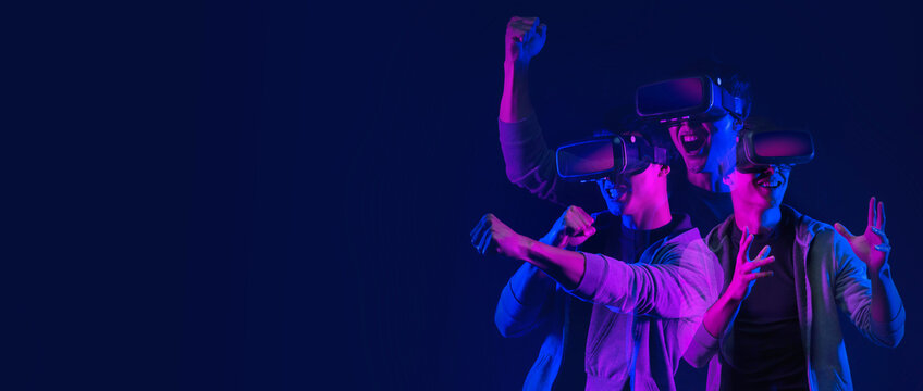 Teenager having fun play VR virtual reality glasses sport game futuristic neon colorful background, future digital technology game and entertainment