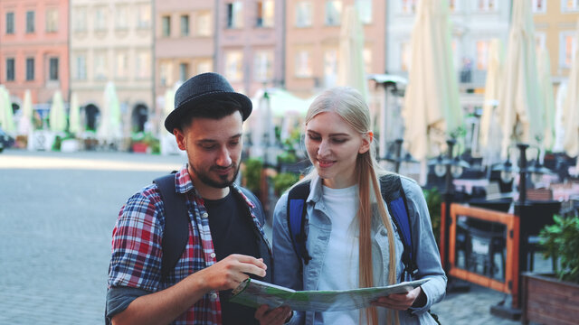 Medium shot of happy young couple of tourists checking map and then smiling to the camera. They standing on a big market square of old european city.