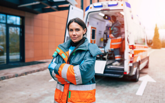 Professional and confident young woman doctor looking on the camera with ambulance background