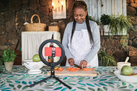 African senior woman streaming online vegetarian cooking virtual masterclass lesson outdoors at home - Influencer concept - Focus on hands