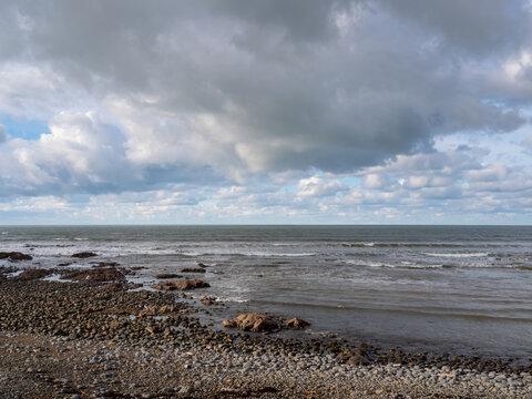 Wintry pebble beach, UK, generic, with stormy grey sky.