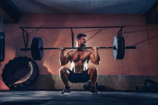 Muscular fitness man doing push a barbell over his head in his garage, selfisolation. Functional training. Snatch exercise.