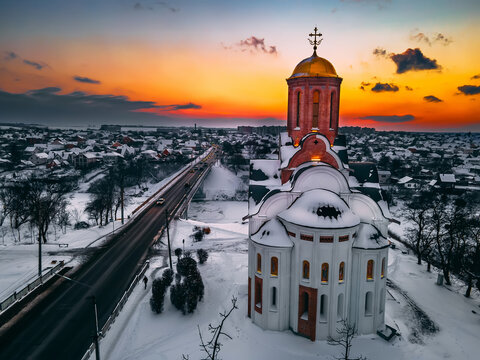 Aerial view of the church in snow-covered small european city at bright winter sunset