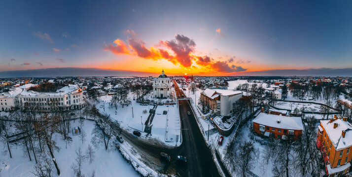 Panoramic aerial view of the cathedral and church in snow-covered small european city at bright winter sunset