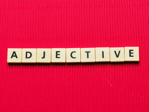 ADJECTIVE word made from square letter tiles on red background.