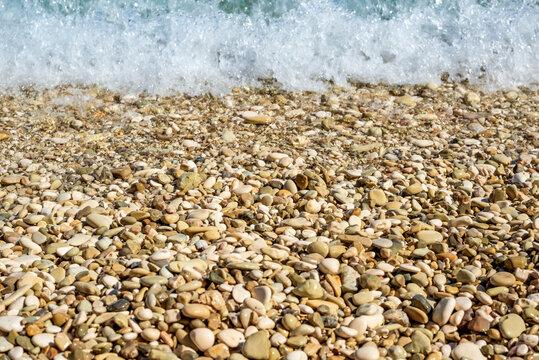 Pebbly stony beach or shore and white sea wave foam.