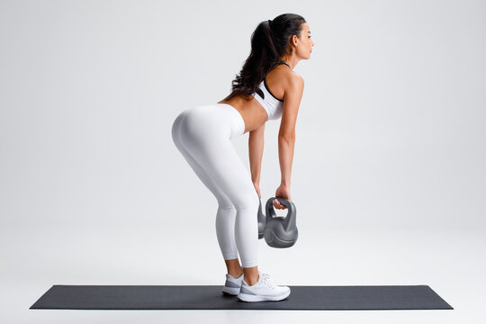 Fitness woman doing deadlift exercise for glutes on gray background. Athletic girl working out with kettlebells