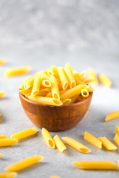 Uncooked yellow pasta in a wooden bowl on gray table. Selective focus. Italian food concept. Copy space