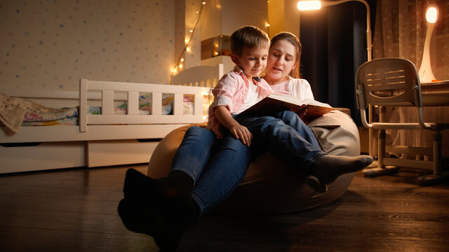 Portrait of little boy listening to fairy tale his mother is reading at night. Concept of child education and family having time together at night