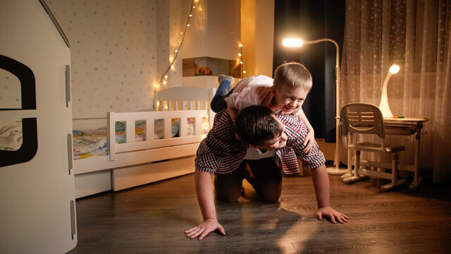 Happy laughing little boy jumping on father's back and riding on him. Concept of child playing with parents and family having time together at night