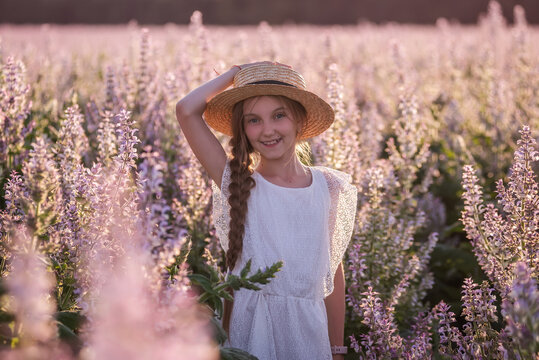 Portraits Beautiful teenage girl in a straw hat, with a long plait in a blooming pink sage field. White sundress. Floral background in sunset light. Rest in the countryside. Copy space, close up
