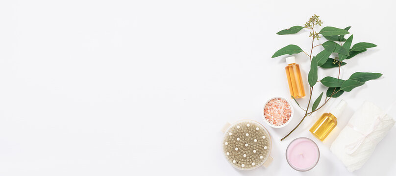Spa and wellness set with fresh eucalyptus branch, Himalaya salt, essential oils, brush for dry massage and aromatic candle on white background. Long banner format.