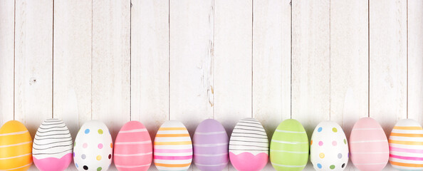Colorful Easter Egg long bottom border. Top view against a white wood banner background. Copy space.