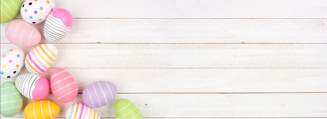 Colorful Easter Egg corner border. Overhead view against a white wood banner background. Copy space.
