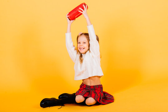 Young cute girl smiling and dancing with wireless portable speaker on yellow studio background.